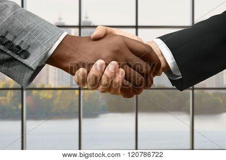 Businessman shake hands at daytime.