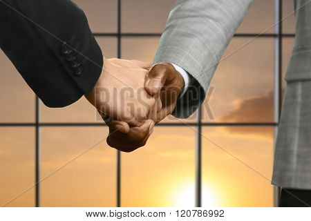 Businessmen shake hands beside window.