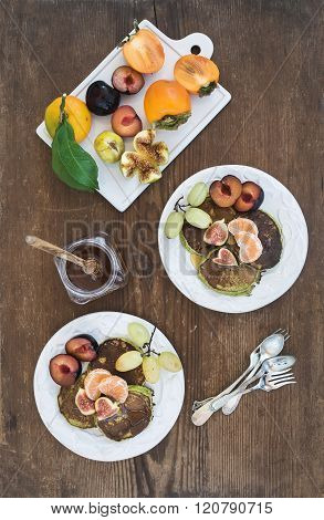 Breakfast set. Homemade zuccini pancakes with fresh plum, tangerine, grapes, figs and honey in white ceramic plates over rustic wooden background, top view