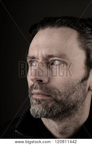Portrait of a man thinking on a dark background