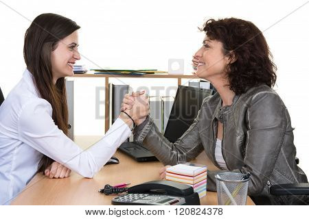 Two Women Wrestling With Hands Clasped At Office Symbol To Win