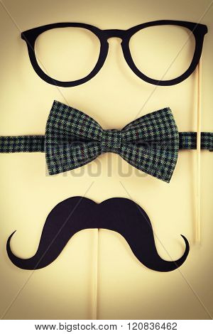 Photo booth props glasses, mustache and bow tie on beige background
