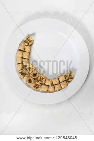 Baklava arranged in a shape of moon on white plate. Ramadan special food - stock image.