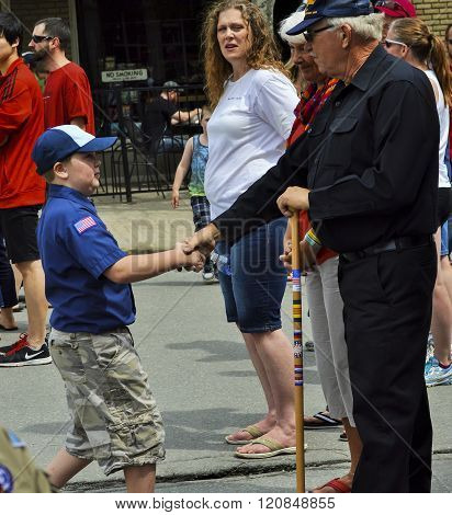 Bangor, Maine/USA-May 25: A uniformed cub scout takes a moment to leave his pack at a parade to shake the hand of a senior military veteran who was watching from the sidelines during the Memorial Day Parade on May 25, 2015 in Bangor, Maine.