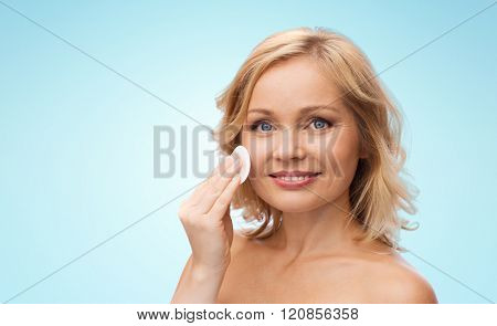 beauty, people and skincare concept - young woman cleaning face and removing make up with cotton pad over blue background