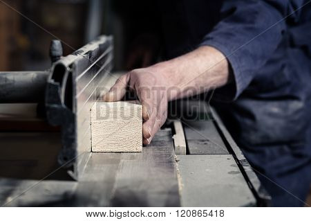 Carpenter's Hands Cutting Wood With Tablesaw