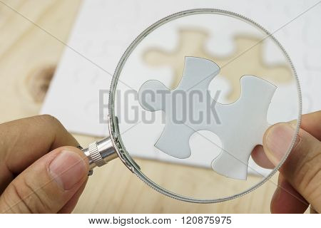 Hand with magnifying glass searching for missing piece of jigsaw puzzle.