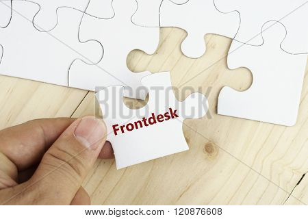 Hand holding piece of jigsaw puzzle on wooden surface