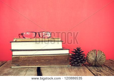 Vintage Still Life Of Stack Of Old Books With Glass And Pine Seed On Red Or Pink Background.