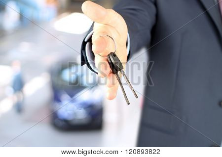 Real-estate agent giving a house key. The plan of a flat and contract behind