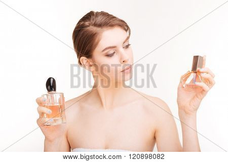 Beauty portrait of attractive young woman holding two bottles of parfums over white background