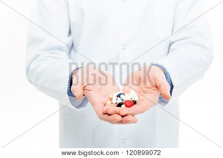 Male doctor holding pills isolated on a white background