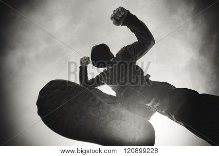 Street violence victim being punched and mugged by aggressive violent man in hooded jacket on street victim's pov perspective monochromatic black and white image. poster