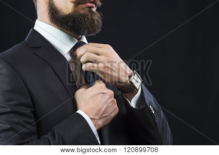 Elegant bearded businessman in suit tying up his tie. Preparation for work.