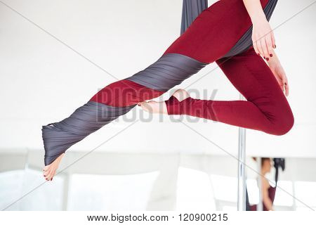 Closeup of young woman legs in leggins practicing aerial yoga in studio