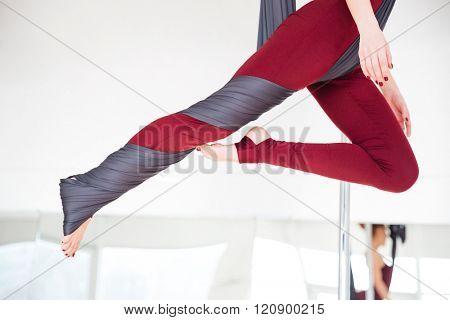 Closeup of young woman legs in leggins practicing aerial yoga in studio