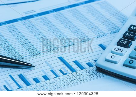 Accounting financial spreadsheet data with pen and calculator in blue