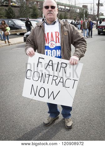 MAR 5, 2016 - WOODBRIDGE, NJ: A New Jersey Transit rail worker holds a sign that says Fair Contract Now to support the coalition of rail labor unions at a rally one week before the strike deadline.