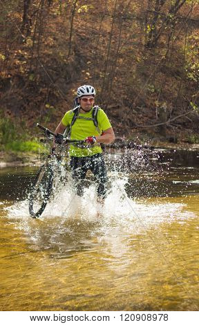 A man passes a river with a bicycle on his shoulder in a helmet and a backpack.