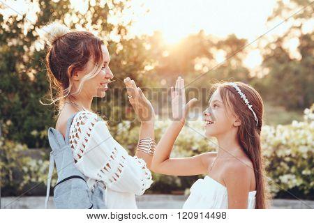 Tween daughter holding hands her mom in summer sunlight