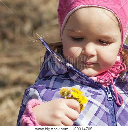 Little Girl Sees Bunch Of Yellow Spring Flowers
