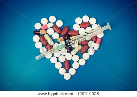 A syringe on medicine arranged as a heart shape