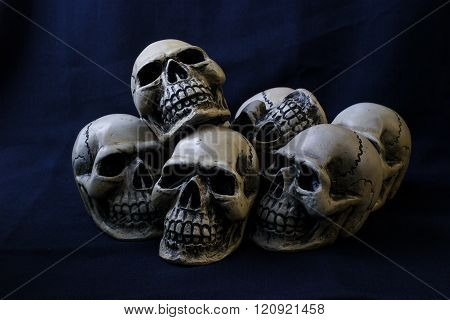 Still life photography concept with human skull on dark blue fabric