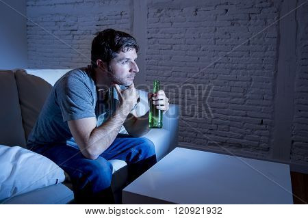 young television addict man sitting on home sofa watching TV and drinking beer bottle looking mesmerized enjoying movie sitcom or live sport at night