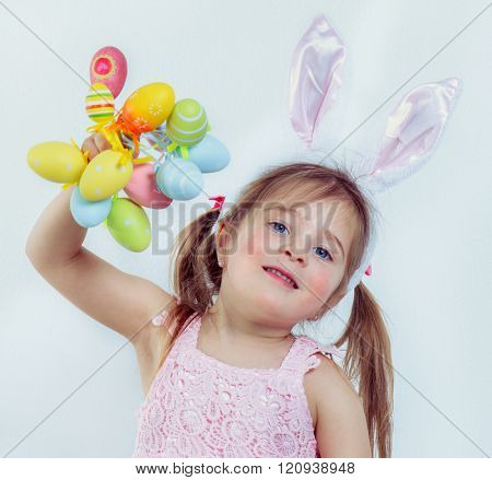 Smiling preschool kid with Easter bunny ears on holding a bunch of colorful eggs
