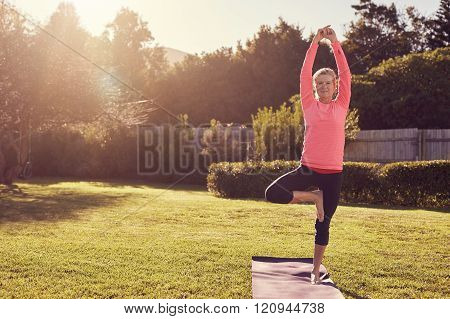 Senior woman in balancing yoga pose with morning sunflare