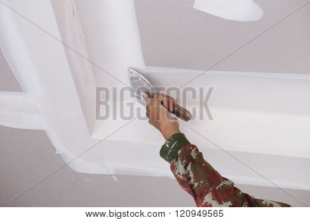 hand of worker using gypsum plaster ceiling joints at construction site poster