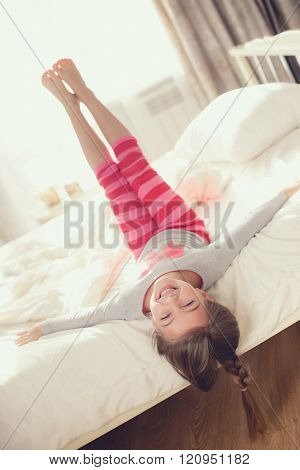 Child doing exercises while lying in bed
