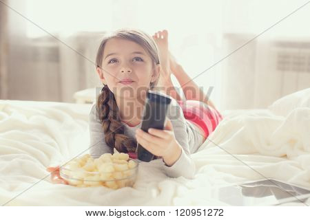 A beautiful little girl 6 years old,brunette with long hair are braided in a braid, dressed in a gray t-shirt and pink striped pants, the house lies on white bed near the window with the remote control for the TV in one hand and eats popcorn