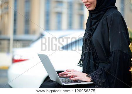 Emarati Arab Business woman using laptop in Dubai, United Arab Emirates.