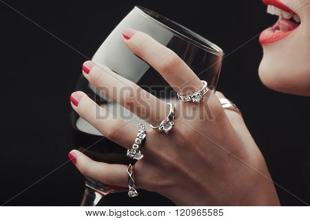 Woman Tasting wine hands all in rings close -up