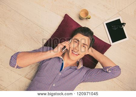 Top View Photo Of Man Lying On The Floor And Talking On Phone