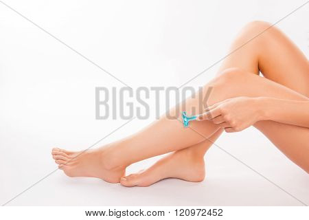 Closeup Photo Of Young  Woman Shaving Her Leg With Blue Razor