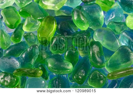Close Up Of Green And Blue Pebbles On A Sea Shore Or River Bed
