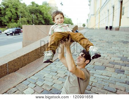 little son with father outside hagging and smiling, city lifestyle concept
