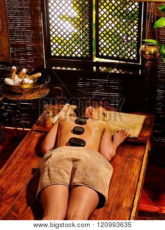 Lying young woman with black stones on back having Ayurveda massage.