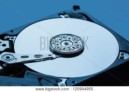 Hard disk drive open inside cylinder plates look head blue macro close up