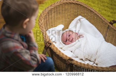 Little Boy Watching Over His New Born Baby Sister