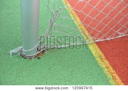 Close Up View Of A Rubber Broken Tennis Net. Untidy Land