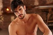 Portrait of handsome young man with bare chest. poster