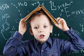 Portrait of little boy tired of studying with a book on his head in front of a green blackboard with formulas. Genius boy near blackboard with formulas. Funny portrait clever pupil boy on school board background. Back to school poster