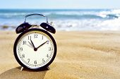 closeup of an alarm clock on the sand of a beach adjusting forward one hour at the beginning of the summer time poster