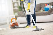 Housewife from cleaning service cleans carpet with vacuum cleaner poster