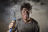 young man holding electrical cable smoking after domestic accident with dirty burnt face in funny sad expression in electricity DIY repairs danger concept in black smoke background poster