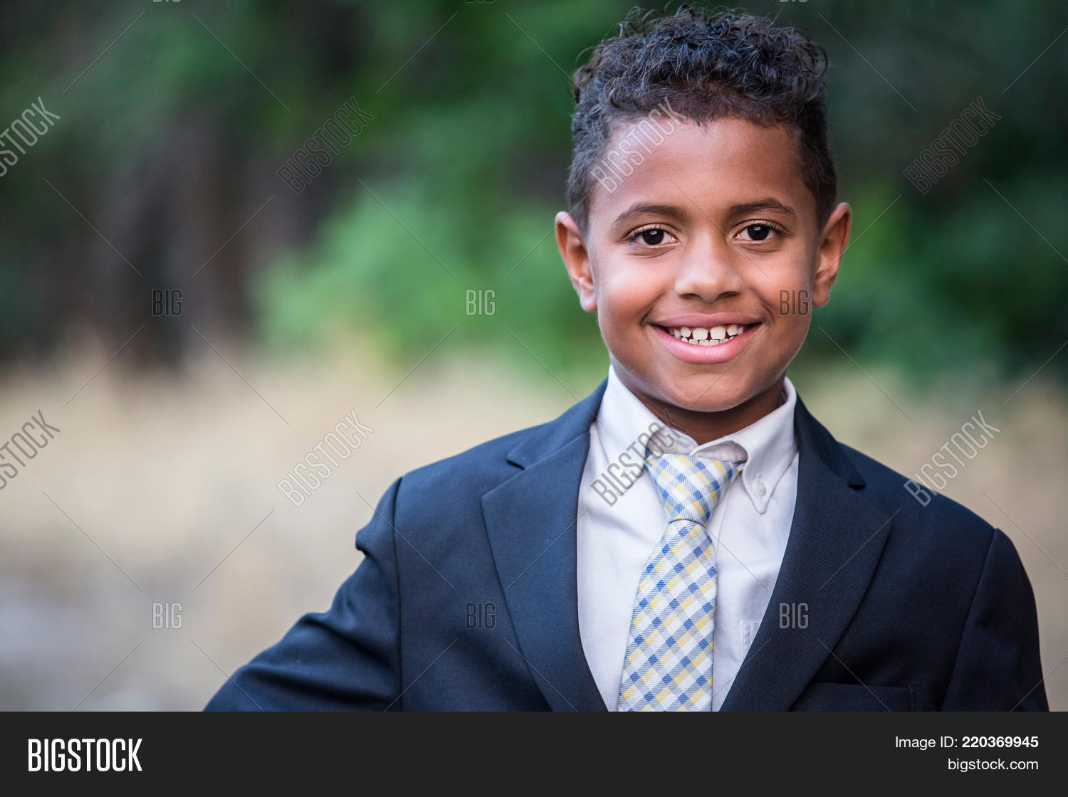5660ef82943 Portrait of a handsome young African American boy in formal clothing.  Smiling with his arms