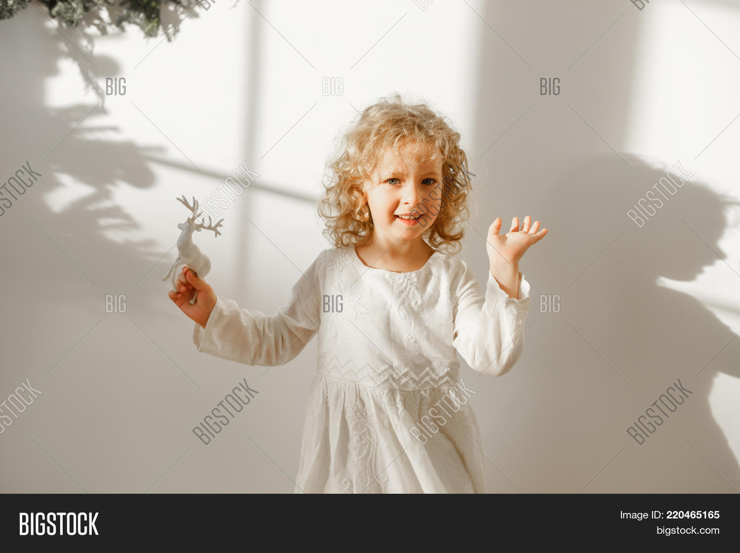 219f281a2028 Playful cheerful little beautiful girl with blonde curly hair plays with  toy deer, dressed in